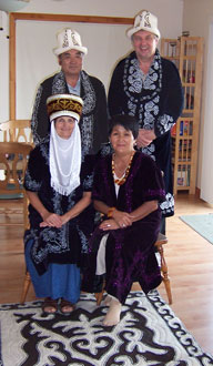 The parents in traditional Kyrgyz dress in front of a traditional Kygyz rug